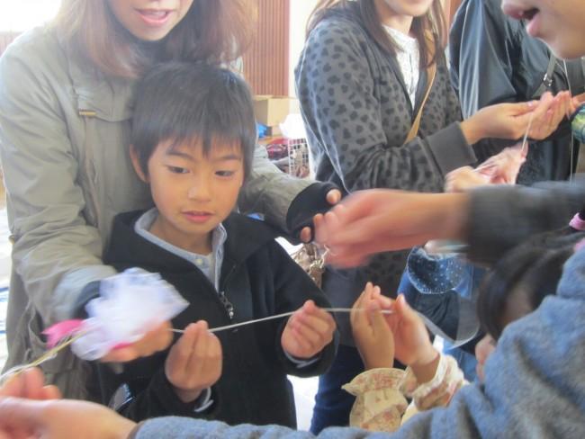 糸の先にはリボンのお花がつけられて、手から手へ渡っていきます。